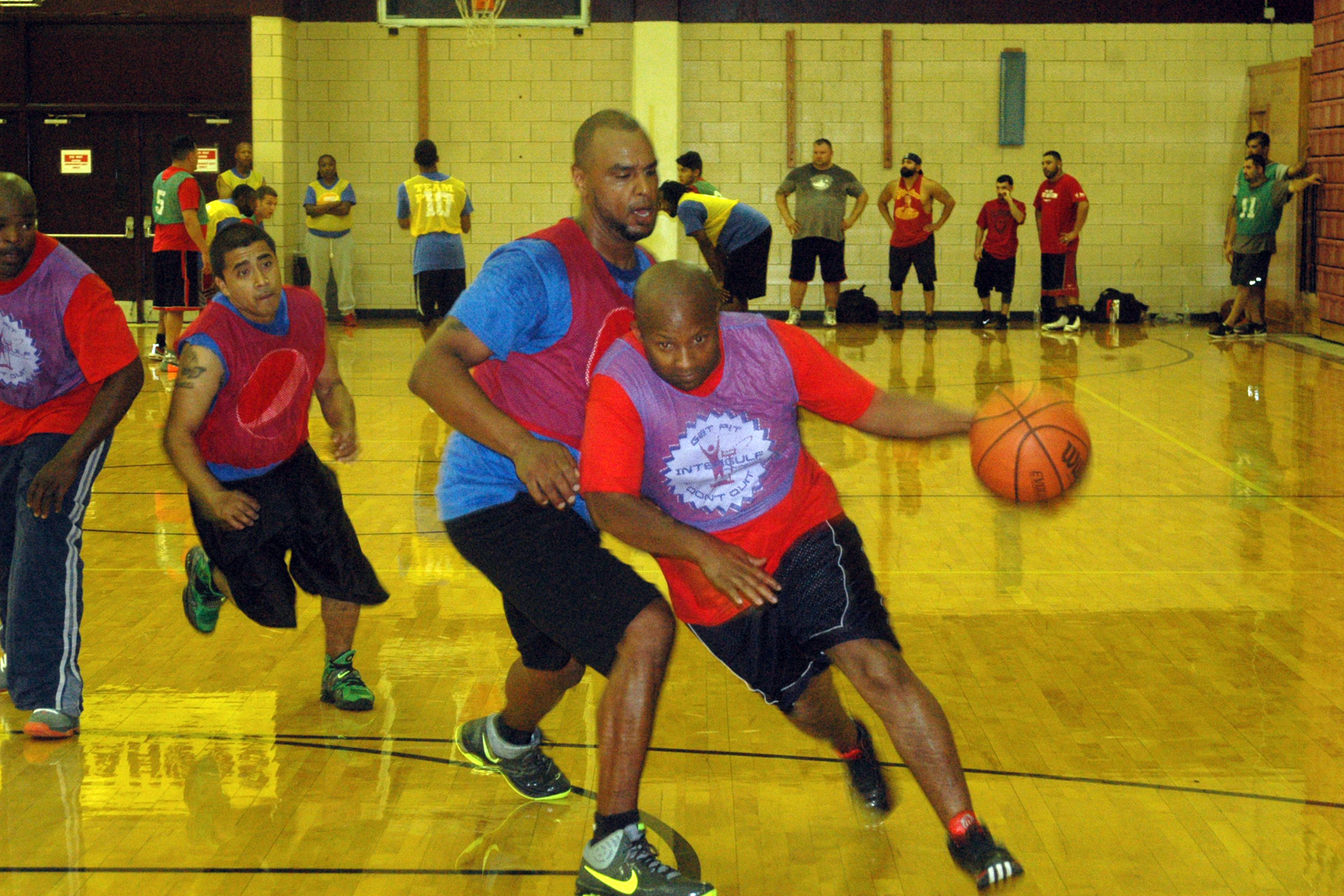 Basketball players chasing man dribbling basketball